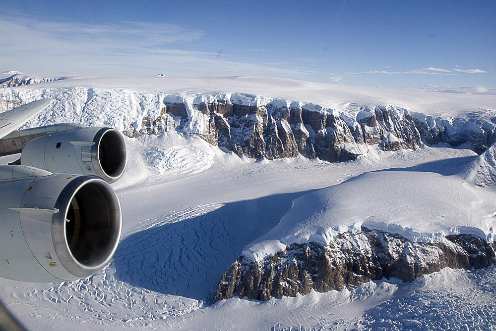 Airplane wing and engine over a snow covered valley
