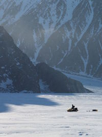 Person using snow mobile to cross a snow covered valley